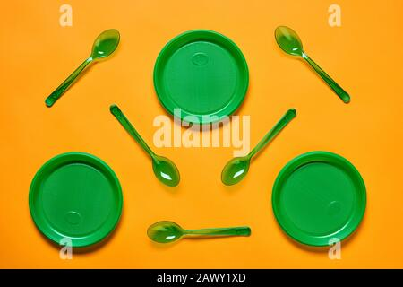 Horizontal flat lay conceptual shot of green plastic spoons and plates on bright orange background - Stock Photo