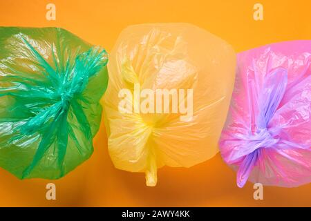 Horizontal from above conceptual shot of three multi-coloured plastic bags full of air on orange background