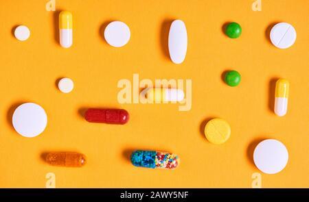 Colourful medicaments on yellow background horizontal flat lay pattern shot - Stock Photo