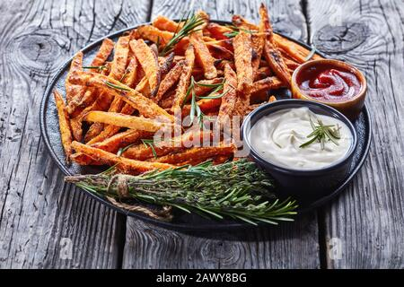 crispy Sweet Potato Fries baked in oven served with sour cream and ketchup on a black platter on a rustic wooden table, close-up - Stock Photo