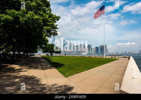 New York, USA - June 7, 2019: American flag on Ellis Island in New York Harbor and Manhattan skyline