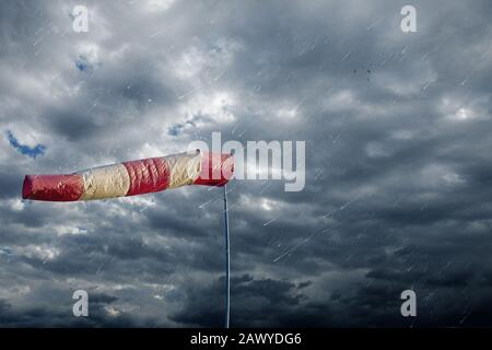 Air sock measuring the wind speed at stormy weather. Hurricane, tornado and storm concept. - Stock Photo