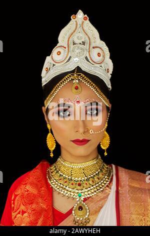 Bengali bride in traditional wedding saree and makeup, face closeup, looking at camera - Stock Photo