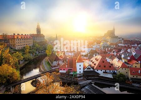 Classic panoramic view of historic city of Cesky Krumlov with famous Castle in beautiful golden morning light at sunrise with mystic fog in fall - Stock Photo