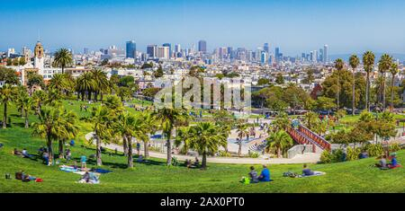 Panorama view of people enjoying the sunny weather on a beautiful day with clear blue skies with the skyline of San Francisco in the background, Calif Stock Photo