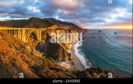 Scenic panoramic view of historic Bixby Creek Bridge along world famous Highway 1 in beautiful golden evening light at sunset, California, USA - Stock Photo