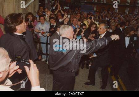 """Frank Sinatra, Royal Albert Hall, London, 1989. Sinatra arriving at Royal Albert Hall, shaking hands with fans and wearing jacket with the words """"I Wanna Go Home"""".  In April 1989, three of the greatest icons of American popular music, Frank Sinatra, Liza Minnelli and Sammy Davis Jr, came together in Frank, Liza and Sammy: The Ultimate Event. - Stock Photo"""