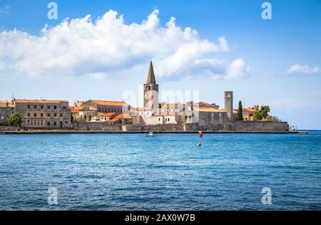 Scenic panoramic view of the historic skyline of adriatic town of Porec with deep blue water on a sunny day in summer, Istria, Croatia - Stock Photo