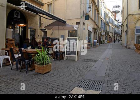 People sitting outside cafes in Rue de l'Université, old quarter, Montpellier, France - Stock Photo