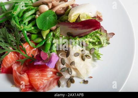 Close-up of dish of marinated salmon in beet and dill. Perona green beans, pickled fennel, green asparagus, marinated mushrooms and pumpkin seeds. Iso - Stock Photo