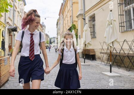 Children going to school, two girls sisters walking together, holding hands - Stock Photo