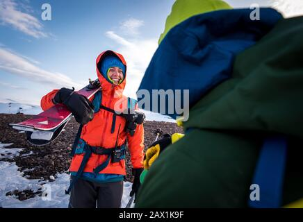 Woman talking with man with skis in Iceland - Stock Photo