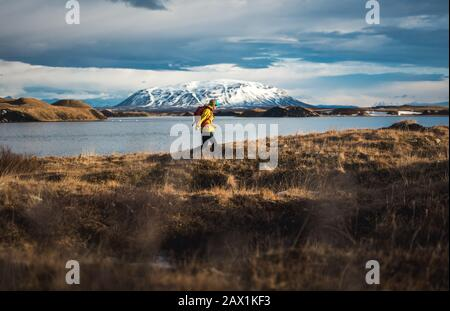 Woman walking through field next to lake with mountains in distance