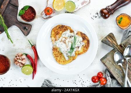 Potato pancakes with mushroom sauce. On a wooden background. Top view. Free space for your text. - Stock Photo