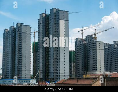 High rise apartment tower blocks under construction towering above traditional buildings,  Jining, China, Asia - Stock Photo
