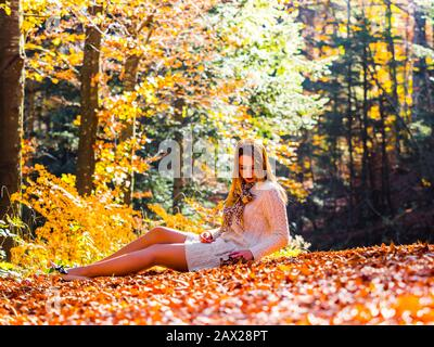 Autumn in forest teen girl sitting reclined on ground full length whole body sideview side-view serious looking down hand holding fallen leaves - Stock Photo