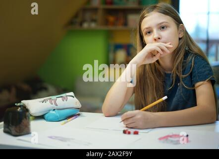 young girl focused on drawing at home