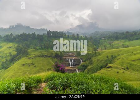 Beautiful waterfall among green hills under cloudy mountains, St. Clairs Falls, Sri Lanka - Stock Photo