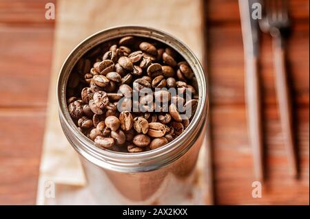 Coffee beans in a can. Roasted aromatic coffee close-up. Sunlight on background