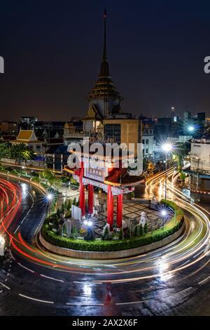 Night view of traffic around the Odeon Circle showing architectural landmark Chinatown Gate in Bangkok, Thailand. - Stock Photo