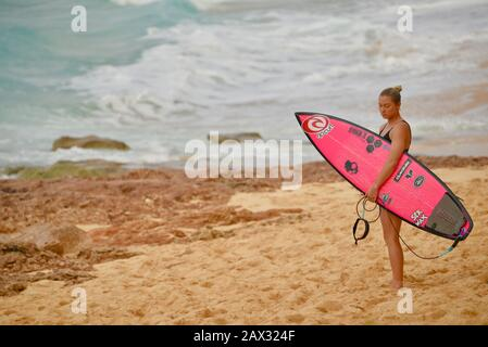 Female surfer holding pink surfboard on beach after riding massive waves  in Banzai Pipeline on North Shore, Oahu island, Haleiwa, Hawaii, USA - Stock Photo