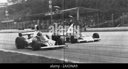 'Italiano: Monza, Autodromo Nazionale, 7 settembre 1975. XLVI Gran Premio d'Italia. Il pilota della Scuderia Ferrari, l'austriaco Niki Lauda (n. 12, in primo piano) su Ferrari 312T, viene superato dal campione del mondo in carica della McLaren, il brasiliano Emerson Fittipaldi (n. 1, in secondo piano) su McLaren-Ford M23C.Uno dei segreti di Niki Lauda è il complesso-Fittipaldi, di cui l'austriaco non ha mai fatto mistero di soffrire. Se n'è avuta una dimostrazione proprio a Monza, quando Niki non ha reagito al sorpasso del brasiliano all'ingresso della chicane, a pochi giri dalla conclusione d - Stock Photo