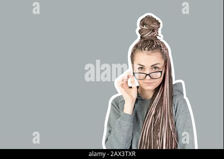Beautiful strict girl with pink pigtails zizi lowered her glasses and looks behind them at the camera on a gray background with a stroke or frame. Con - Stock Photo