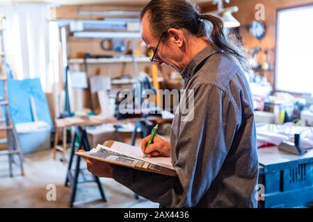 middle aged man with long hair wearing glasses in the garage with tools in the background. home inspector taking professional notes on his notebook