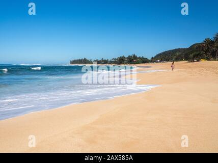 Haleiwa, HI - 24 January 2020: Woman walking on deserted sand at Sunset Beach park on north coast of Oahu, Hawaii - Stock Photo