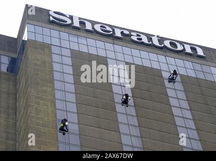New Orleans, Louisiana, U.S.A - February 2, 2020 - Workers hanging cleaning the glass windows from the top of the Sheraton Hotel - Stock Photo