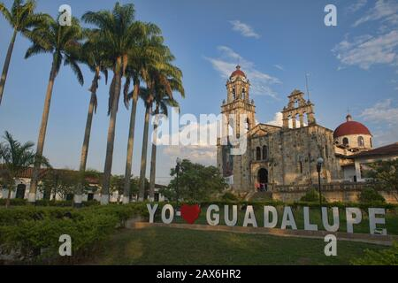 The Parroquia Santuario Nuestra Señora de Guadalupe church and palm tree plaza of Guadalupe, Santander, Colombia - Stock Photo