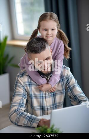 Joyful young dad, little daughter smiling looking at a laptop. - Stock Photo