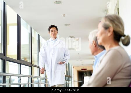 young asian doctor walking in hospital hallway to meet patients in waiting area