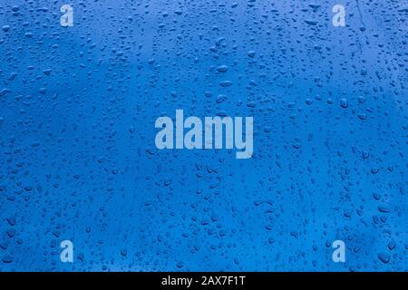 Rain drops on a blue vehicle bodywork. Wet textured background - Stock Photo