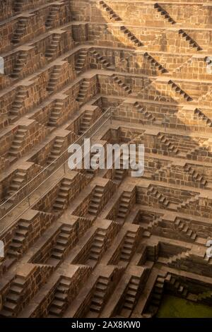 India, Rajasthan, Abhaneri, Chand Baori Stepwell, 13 stories of tiered steps down 30 metres to water - Stock Photo