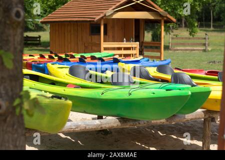 Colorful kayaks placed on racks against the background of a wooden house. Relaxing on the water. Water equipment rental. - Stock Photo