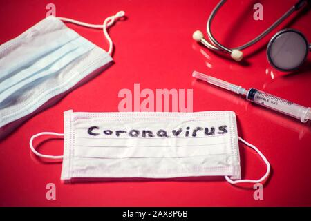Mask with word-coronavirus, medicine items on red background. Medine and healthcare concept - Stock Photo