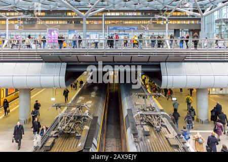 The Hague, The Netherlands - January 15, 2020: Commuters waiting on trains and trams on a two level station platform inside the central station in The - Stock Photo
