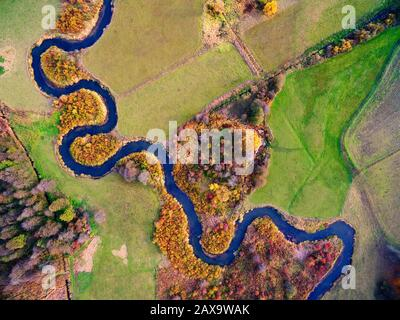 Meander of Goldapa river flowing in the vicinity of Banie Mazurskie during autumn season, Mazury, Poland - Stock Photo