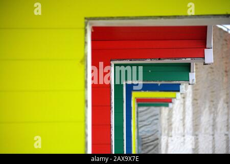 Seaside town in Winter with coloured beach huts and wet sand, the bright colour blocks reflect in the puddles of water - Stock Photo