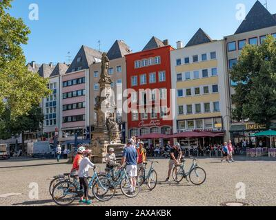 Cologne, Germany. Circa November 2019. Tourists on bicycles visiting the fountain with a statue of Jan von Werth, in the center of the Alter Markt, th - Stock Photo
