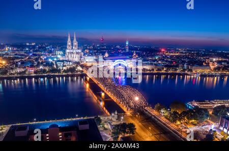 Aerial night panorama of the illuminated Hohenzollern bridge over Rhine river. Beautiful cityscape of Cologne, Germany  with cathedral at dusk. - Stock Photo