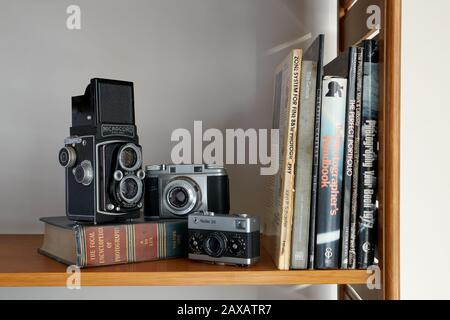 A photograph of three vintage cameras and photography books placed on a shelf. - Stock Photo