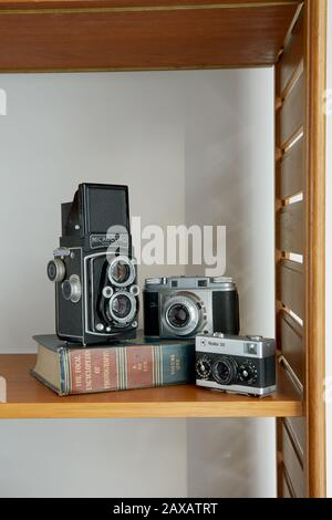 A photograph of three vintage cameras and a vintage photography book placed on a shelf. - Stock Photo