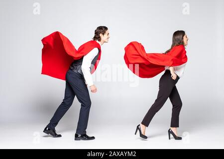 Full length young couple wearing red superhero isolated on white background - Stock Photo