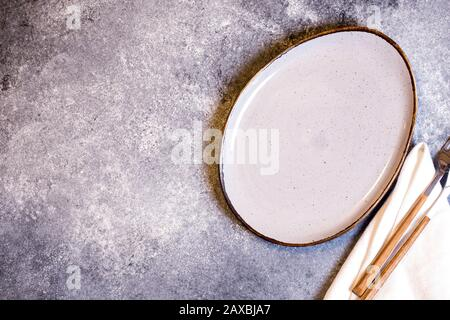Culinary background with empty plate and napkin on a grey slate, stone or concrete table.Top view with copy space - Stock Photo