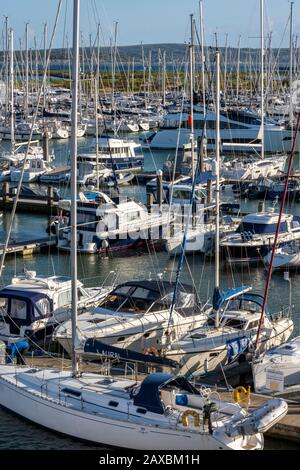 yachts and motorboats moored in the marina on pontoons berths at Lymington marina in the new forest, hampshire, uk - Stock Photo