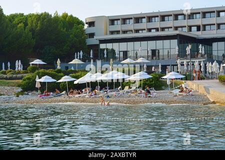 Rovinj, Croatia, August 24: Tourists and residents of Rovinj relax on the pebble beach of red island in Croatia, August 24, 2019. - Stock Photo