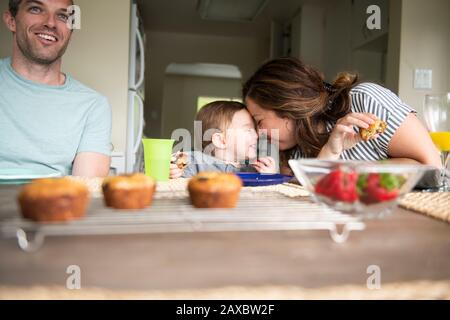 Happy mother and daughter rubbing noses at kitchen table