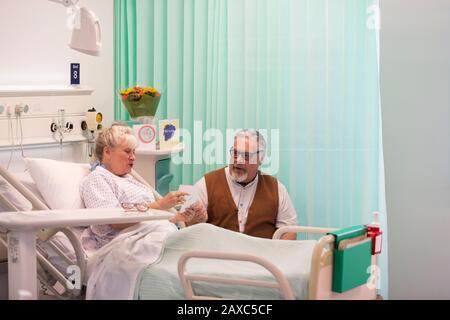 Senior man visiting wife resting in hospital room - Stock Photo